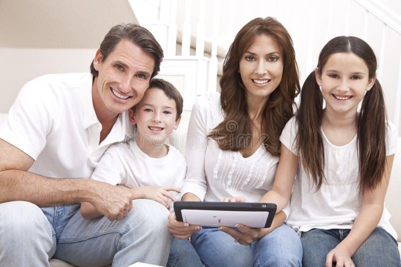 Família feliz que usa o computador da tabuleta em casa