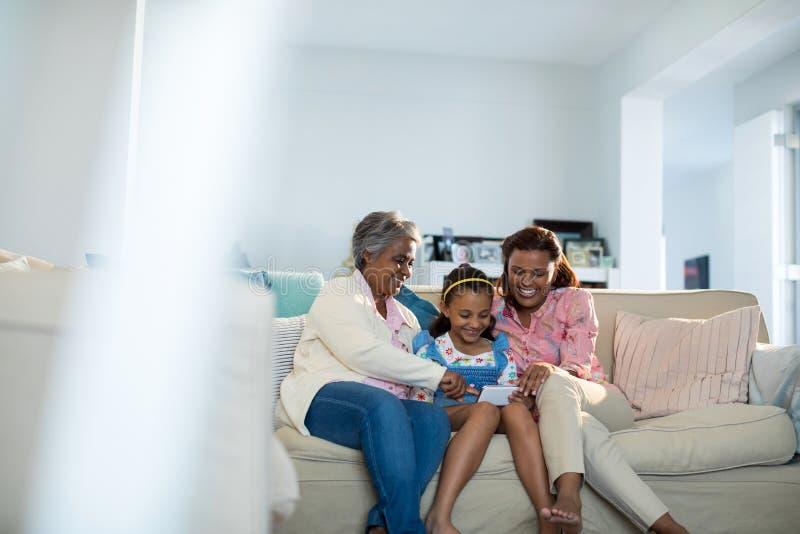 Família feliz que usa o telefone celular na sala de visitas fotografia de stock