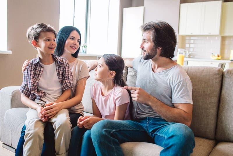 A família feliz senta-se junto no sofá O menino está no regaço do ` s da mãe A menina senta-se entre a mulher e o homem Estão olh foto de stock royalty free