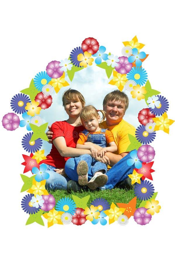A família feliz senta-se na grama verde sob o céu fotografia de stock