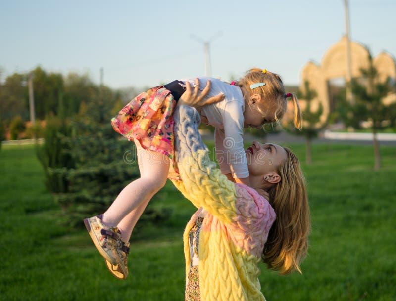 Família feliz Sira de mãe ao jogo com sua filha no gramado verde com grama imagens de stock royalty free
