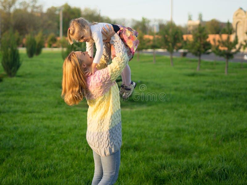 Família feliz Sira de mãe ao jogo com sua filha no gramado verde com grama imagens de stock