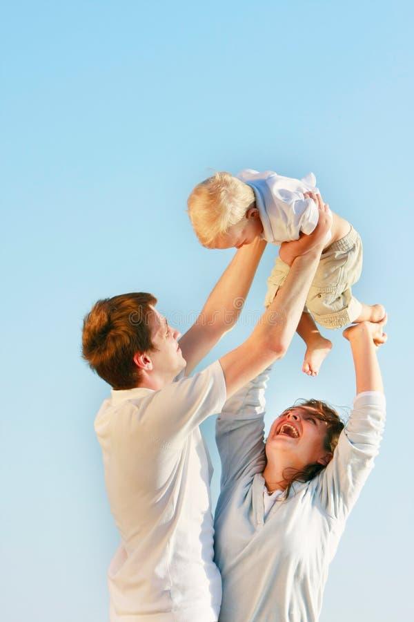Família feliz sobre o céu azul fotografia de stock