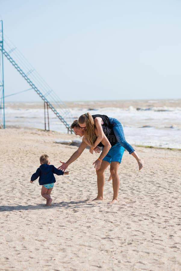 A família feliz tem o divertimento no Sandy Beach fotografia de stock