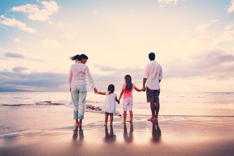 A família feliz tem o divertimento que anda na praia no por do sol