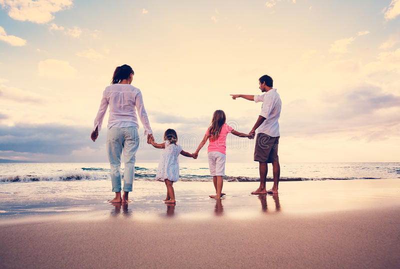 A família feliz tem o divertimento que anda na praia no por do sol fotografia de stock royalty free