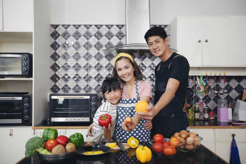 A família feliz tem o paizinho, a mamã e sua filha pequena cozinhando o Tog fotografia de stock