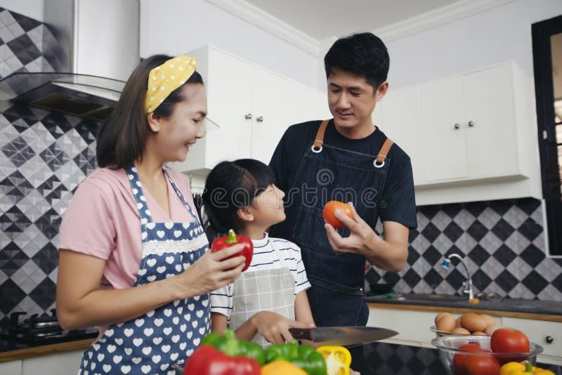 A família feliz tem o paizinho, a mamã e sua filha pequena cozinhando o Tog imagens de stock