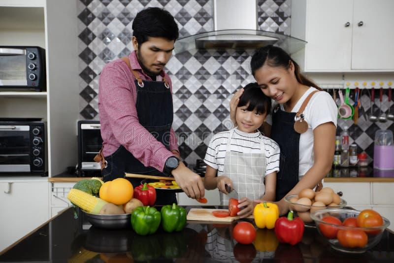 A família feliz tem o paizinho, a mamã e sua filha pequena cozinhando o Tog fotografia de stock royalty free