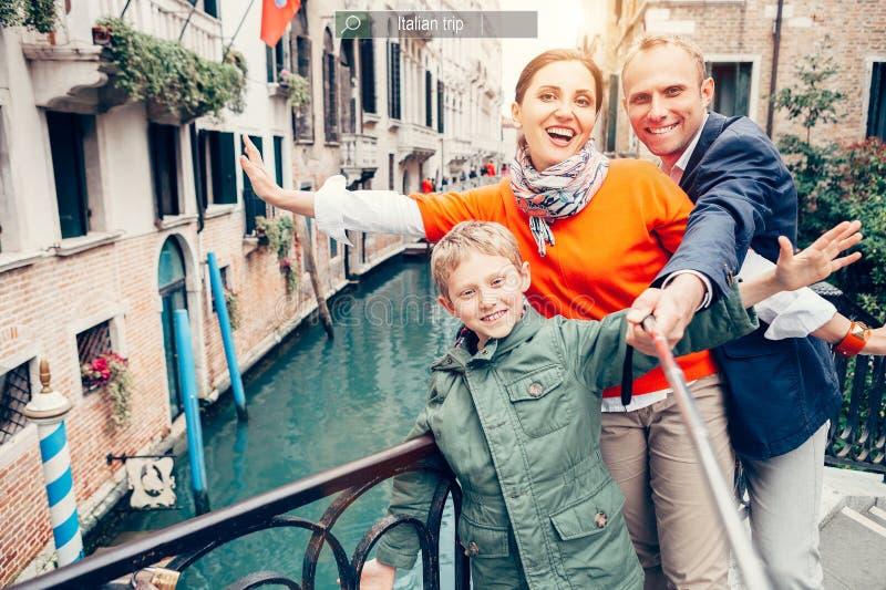 A família feliz toma uma foto do auto em essa das pontes em Veneza fotografia de stock