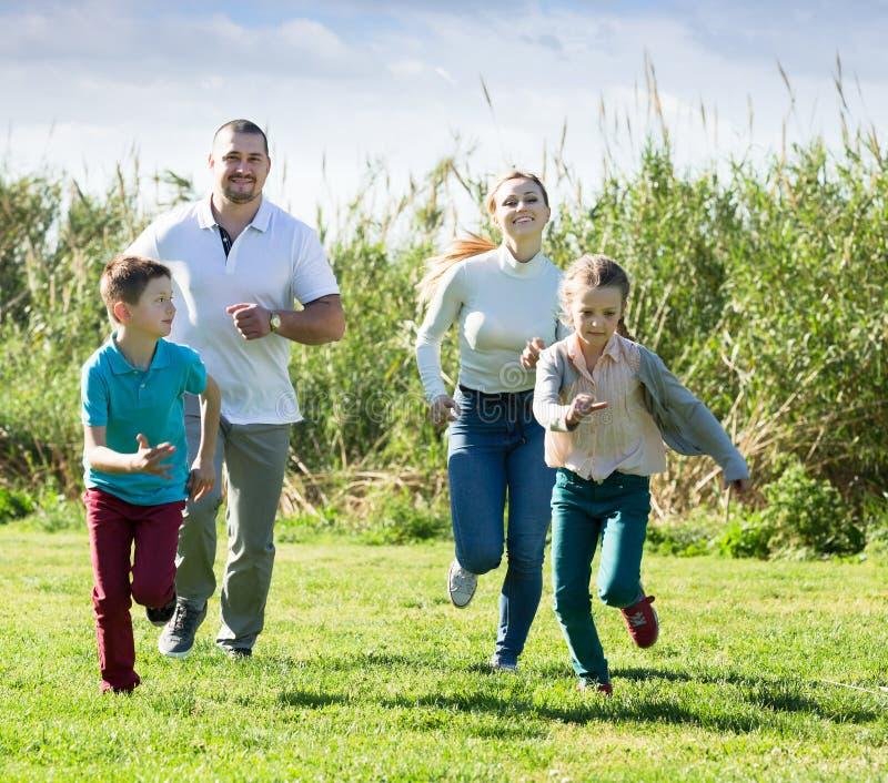 Família felizmente que joga e que corre imagens de stock