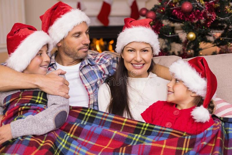 Família festiva no chapéu de Santa que abraça sob a tampa fotos de stock