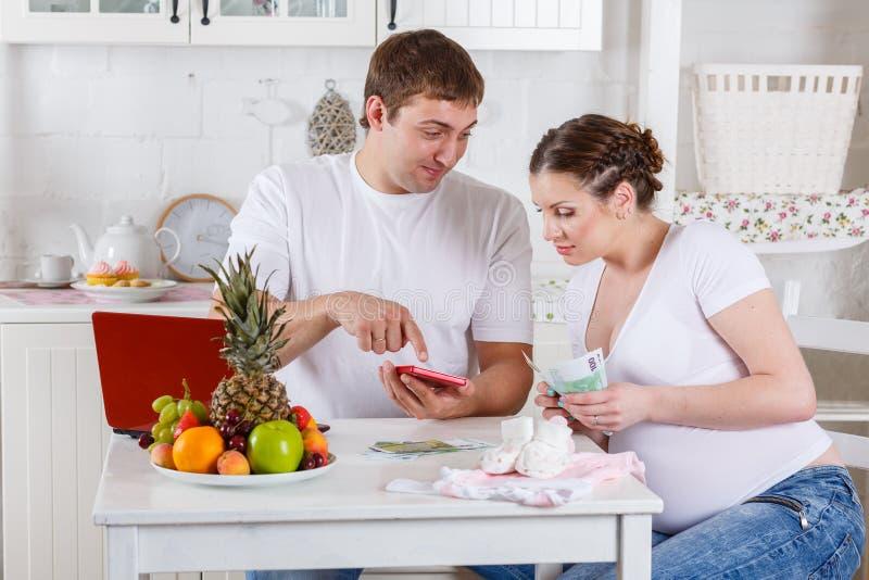 Família grávida com dinheiro. Orçamento de família. fotos de stock