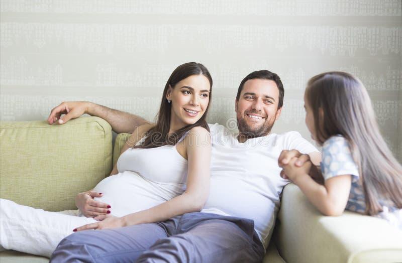Família grávida nova adorável na sala de visitas foto de stock royalty free