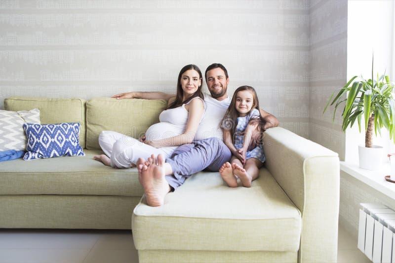 Família grávida nova adorável na sala de visitas imagem de stock
