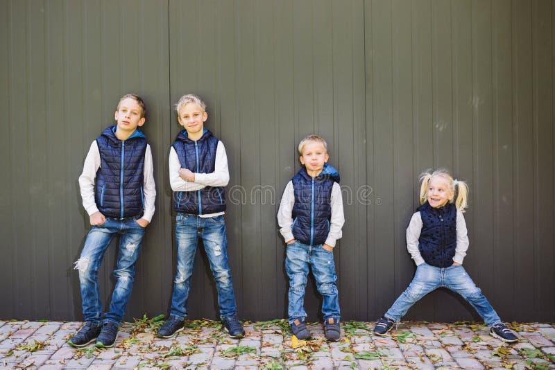 Família grande caucasiano engraçada de três irmãos e de irmã que levantam a posição no fundo do crescimento da parede no crescime imagem de stock