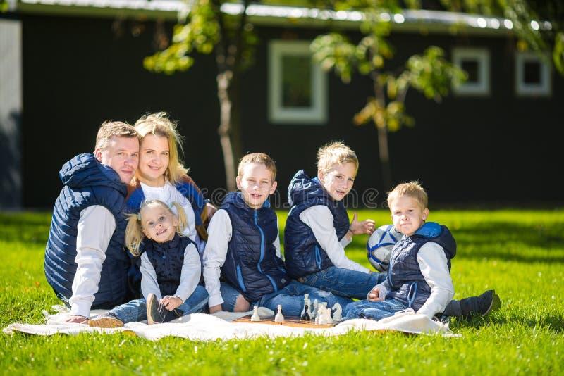 Família grande que relaxa na natureza verde O retrato feliz em exterior, seis pessoas da família do grupo senta-se na grama, temp foto de stock
