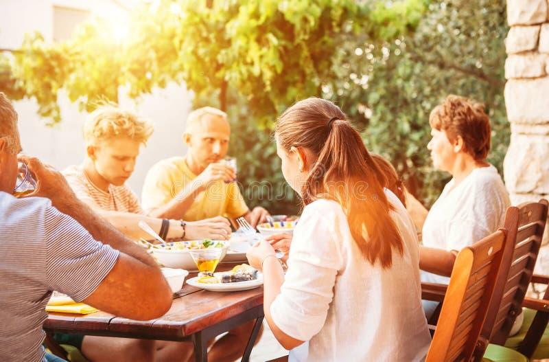A família grande tem o jantar no terraço aberto do jardim fotografia de stock