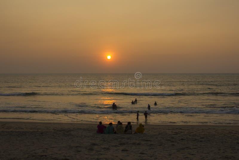 Família indiana grande na praia no tempo do por do sol Mulheres em sarees coloridos fotos de stock royalty free
