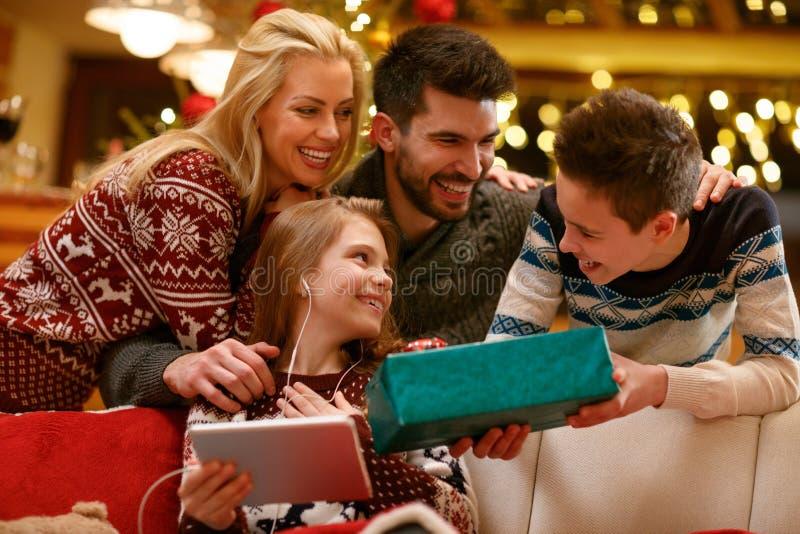 Família junto na Noite de Natal com o presente nas mãos do ` s do menino fotos de stock