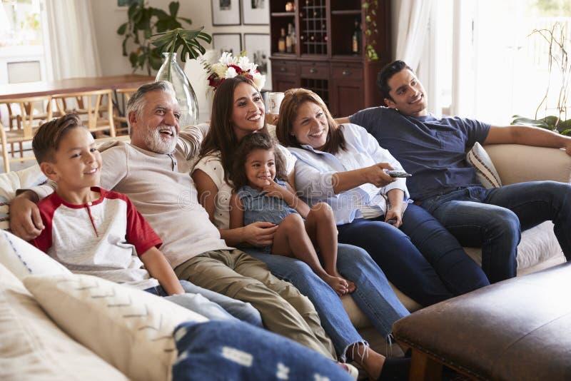 Família latino-americano de três gerações que senta-se no sofá que olha a tevê, avó que usa o controlo a distância fotos de stock royalty free
