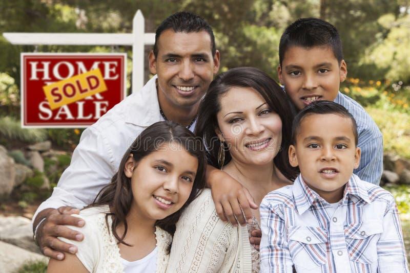 Família latino-americano na frente do sinal vendido de Real Estate fotos de stock royalty free