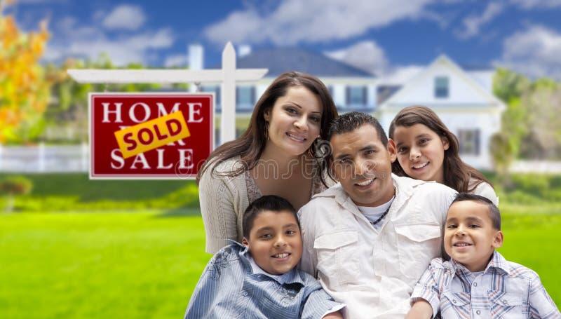 Família latino-americano na frente do sinal vendido de Real Estate, casa imagem de stock royalty free