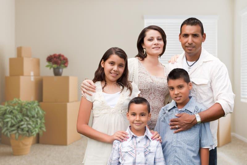Família latino-americano na sala vazia com as caixas moventes embaladas e o Potte imagem de stock