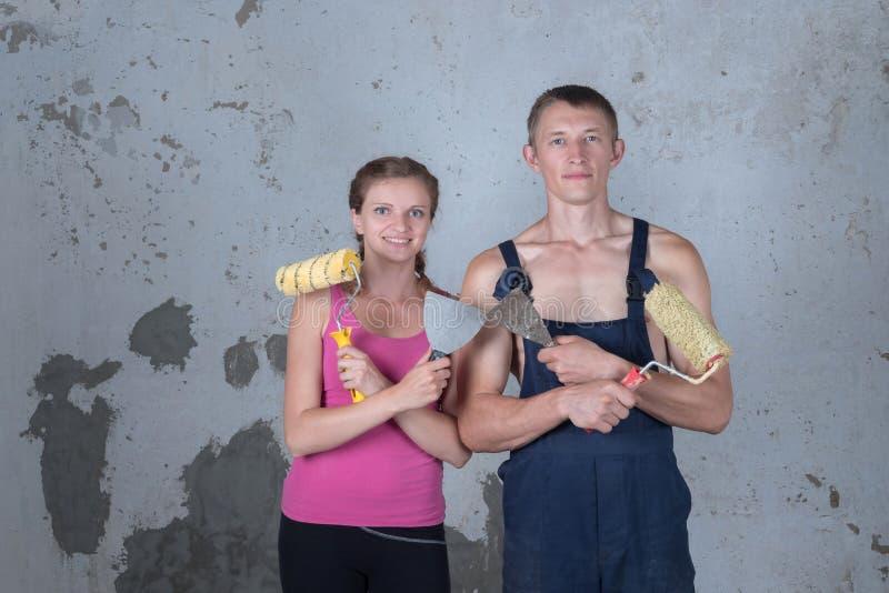 A família loving com pintura dos rolos faz reparos em um separado novo imagens de stock royalty free