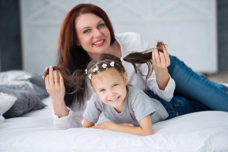 Família loving feliz Sira de mãe e sua menina da criança da filha que joga e que abraça foto de stock royalty free