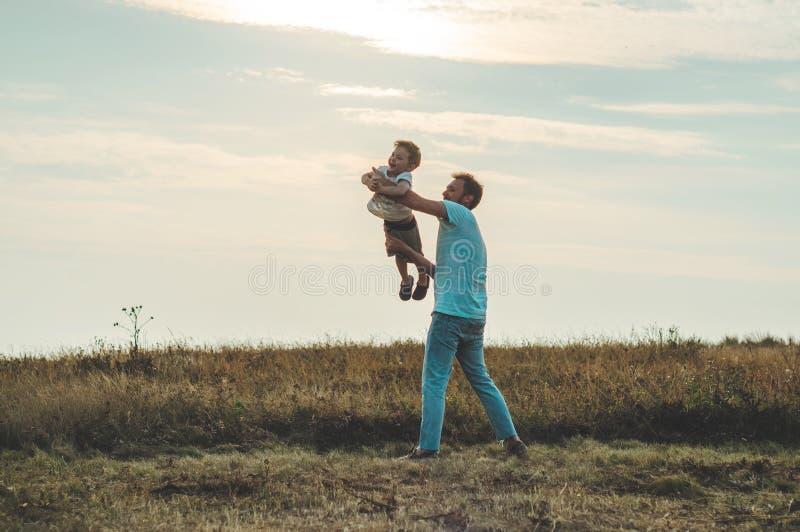 Família Loving Gene e seu bebê do filho que joga e que abraça fora Paizinho e filho felizes fora Conceito do dia do ` s do pai fotografia de stock