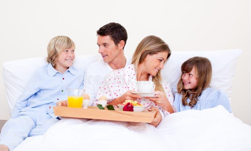 Família Loving que come o pequeno almoço sentar-se na cama imagens de stock