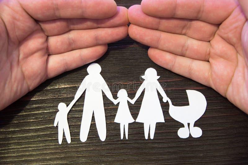 Família loving que guarda as mãos Figuras de papel em um fundo do mogno fotografia de stock royalty free
