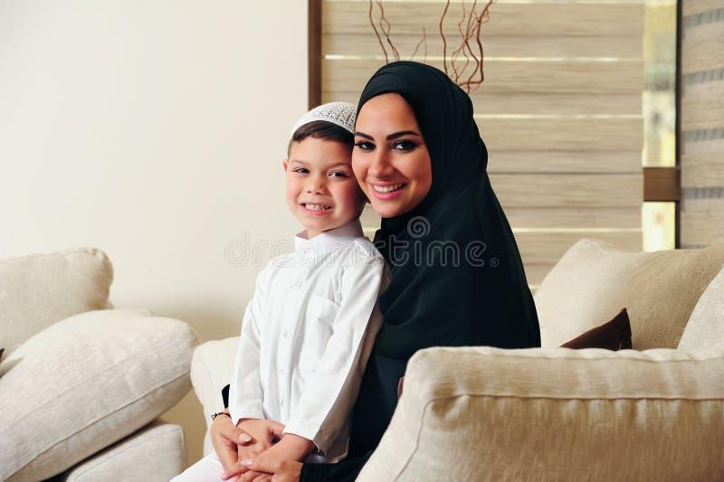 Família, mãe árabe e filho sentando-se no sofá em sua sala de visitas imagens de stock royalty free