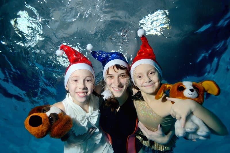 Família: a mãe e duas filhas são nadadoras e de jogos debaixo d'água na associação nos tampões Santa Claus que guarda cães de bri imagem de stock