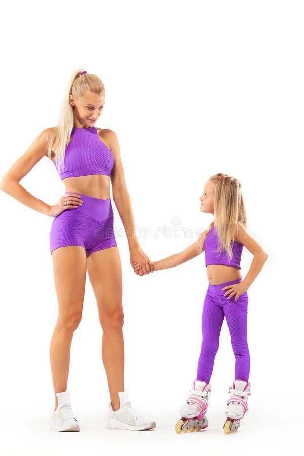 Família, mãe e filha, levantando no estúdio que veste rollerskates inline fotografia de stock royalty free