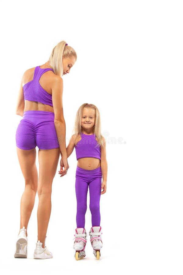 Família, mãe e filha, levantando no estúdio que veste rollerskates inline imagem de stock royalty free