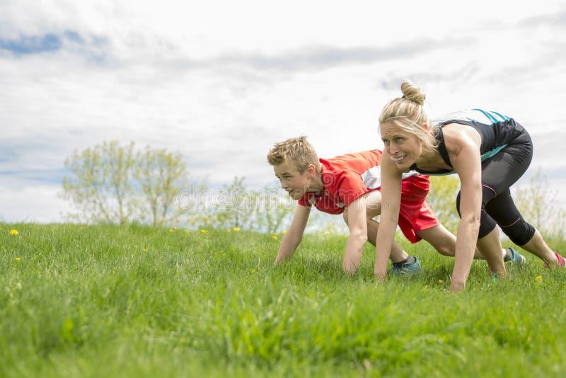 A família, a mãe e o filho são de corrida ou movimentando-se para o esporte fora fotos de stock