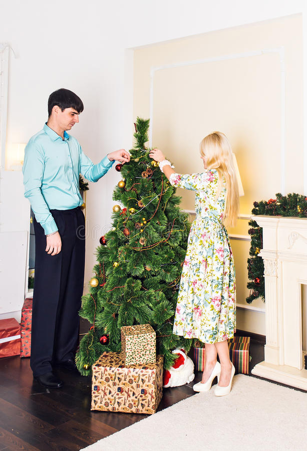 Família, x-mas, feriados de inverno e conceito dos povos - par feliz decorando a árvore de Natal em casa fotografia de stock royalty free