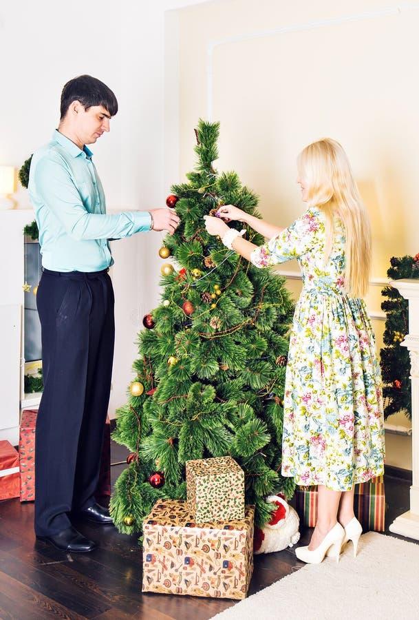 Família, x-mas, feriados de inverno e conceito dos povos - par feliz decorando a árvore de Natal em casa imagem de stock