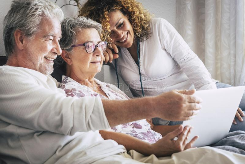 Família moderna em casa que senta e que usa a tecnologia mãe e pai e filho com videoconferência do laptop e do Internet fotografia de stock royalty free