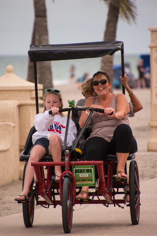 A família monta o triciclo no passeio à beira mar foto de stock royalty free