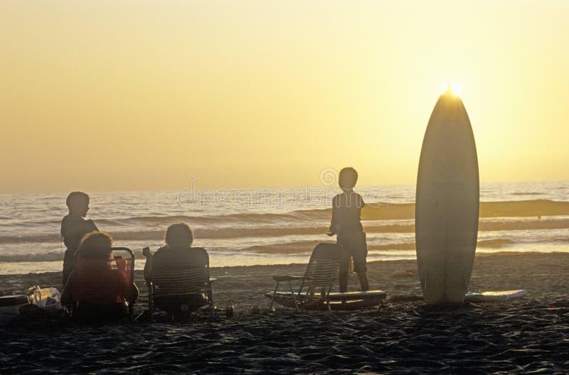 Família mostrada em silhueta na praia no por do sol, San Diego California fotografia de stock royalty free