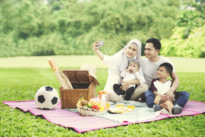 Família muçulmana com o smartphone no parque fotos de stock