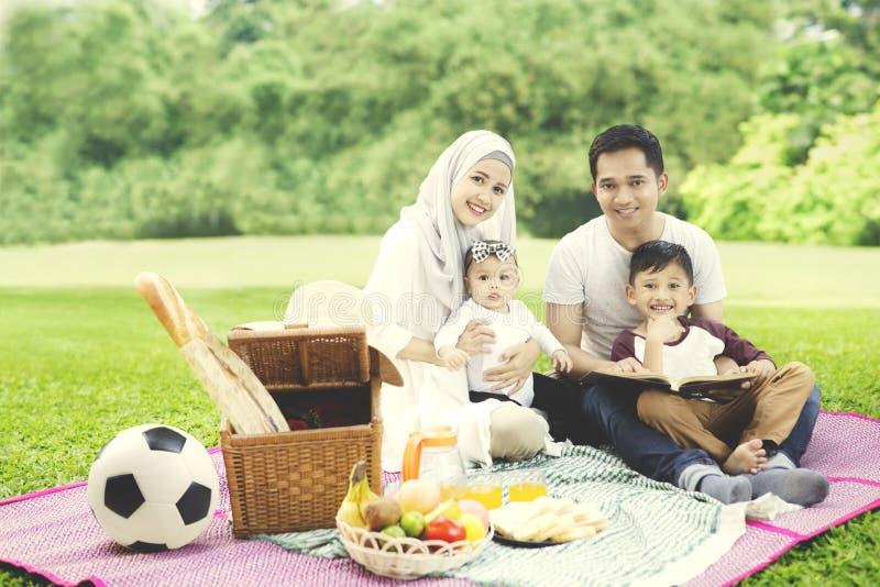 Família muçulmana com um livro no parque imagens de stock royalty free
