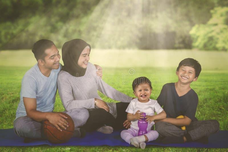 A família muçulmana descansa após o exercício no parque foto de stock