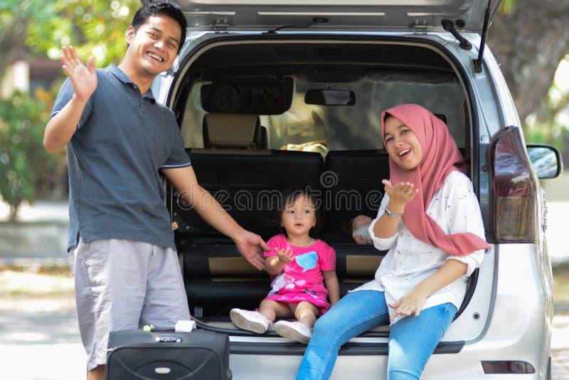 Família muçulmana nova, transporte, lazer, conceito da viagem por estrada e dos povos - homem feliz, mulher e menina que estão e  fotografia de stock royalty free