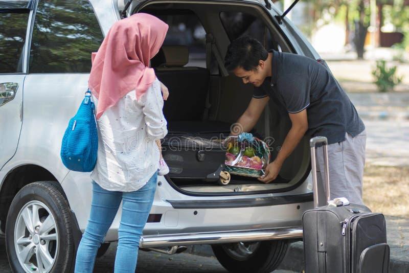 Família muçulmana nova, transporte, lazer, conceito da viagem por estrada e dos povos - homem feliz, mulher e menina que preparam imagens de stock royalty free