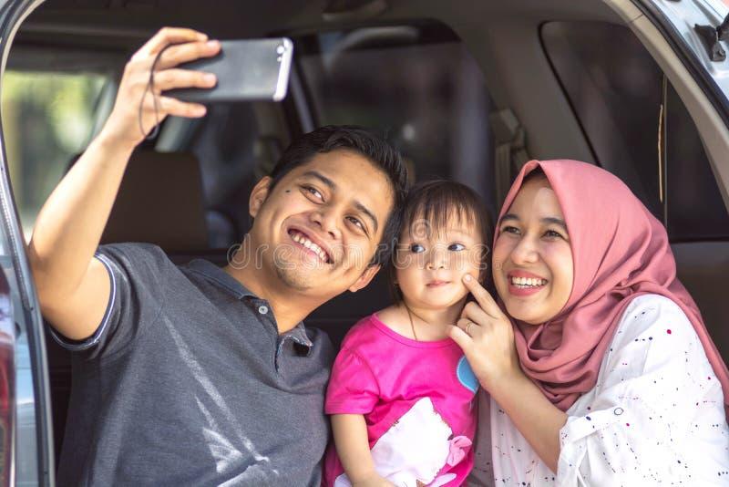 Família muçulmana nova, transporte, lazer, viagem por estrada e conceito dos povos - fim acima do homem, da mulher e da menina fe imagens de stock royalty free