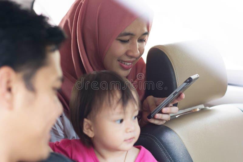 Família muçulmana nova, transporte, lazer, viagem por estrada e conceito dos povos - opinião lateral o homem, a mulher feliz e a  imagens de stock royalty free
